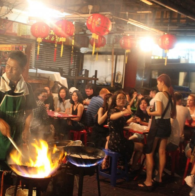 crowd of people seated at tables at a bangkok food stall