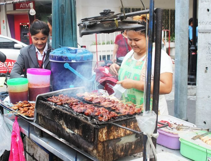 Woman grilling meat at a Bangkok food stall